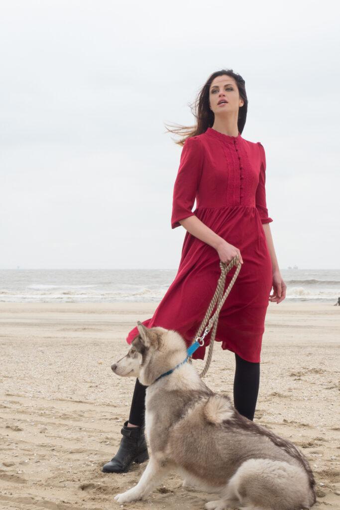 Model met rode jurk met Husky hond aan zee